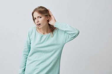 Body language. Young excited Caucasian blonde woman with long hair in blue sweater looking at the camera opened mouth and holding hand behind ear while listening with excitement to incredible story