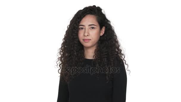 Portrét okouzlující kudrnaté dlouhé vlasy dospělých dívka šťastně ukazuje palcem nahoru izolované na bílém pozadí. Pojetí emocí