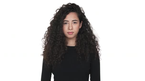 Portrait of pleased female with dark curly hair nodding in agreement  meaning yes over white background  Concept of emotions
