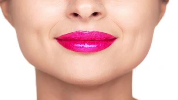Oříznutý portrét veselá žena s světlé kosmetiky na rtech úsměv, znázorňující její štěstí nad bílým pozadím extrémní closeup. Výrazy obličeje