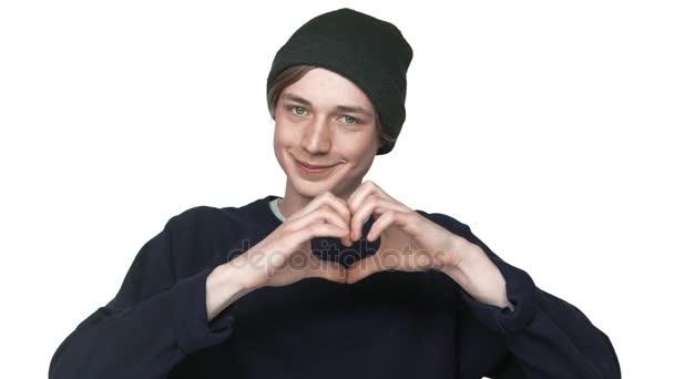 v pomalém pohybu portrét usměvavá Kavkazský mladík nosit klobouk zobrazeno srdce tvar prsty baví Blbnuli kolem nad detailním bílým pozadím. Pojetí emocí