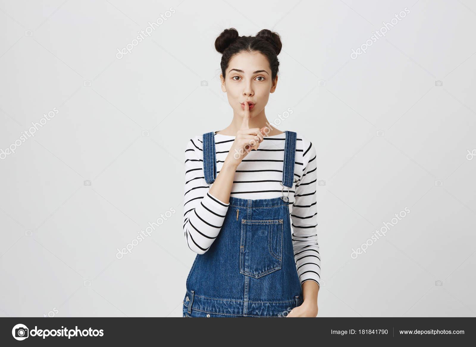 Docela roztomilé žena s tmavými vlasy nosí denim montérky drží prst ... f0fd66c571