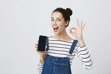 Cute joyful smiling young beautiful female holds modern smart phone, demonstrates it, has joy as uses it, shows ok sign, isolated against gray background. Body language and advertisement concept