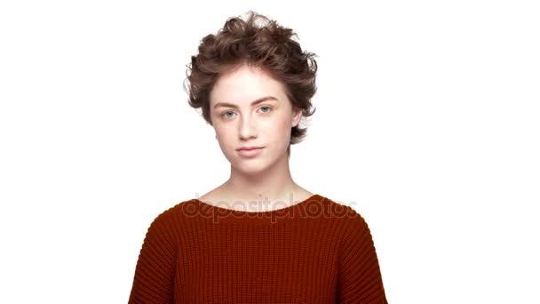 Fotografování portrétů jistý lady s hnědé kudrnaté vlasy, bílé pozadí při pohledu na fotoaparát s smysluplný pohled a úsměv. Pojetí emocí