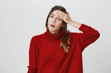Horizontal shot of stressed female office worker in red sweater has headache after hard working day, comes home overworked, keeps hand on forehead, looks desperately at camera, expresses tiredness