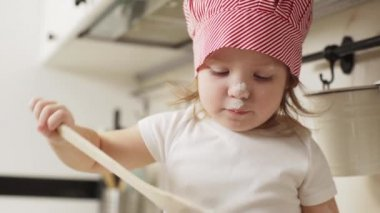 Portrait of baby girl in chief hat having fun while cooking in kitchen, and playing with flour closeup