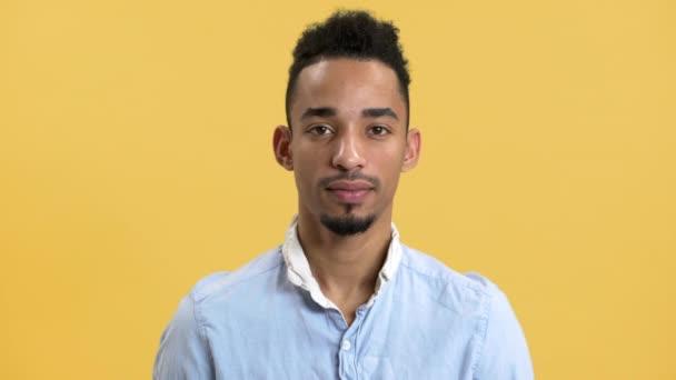 Göndör frizura látszó-on fényképezőgép, izolált át a sárga háttér mulatto fiatalember portréja. Az érzelmek fogalma