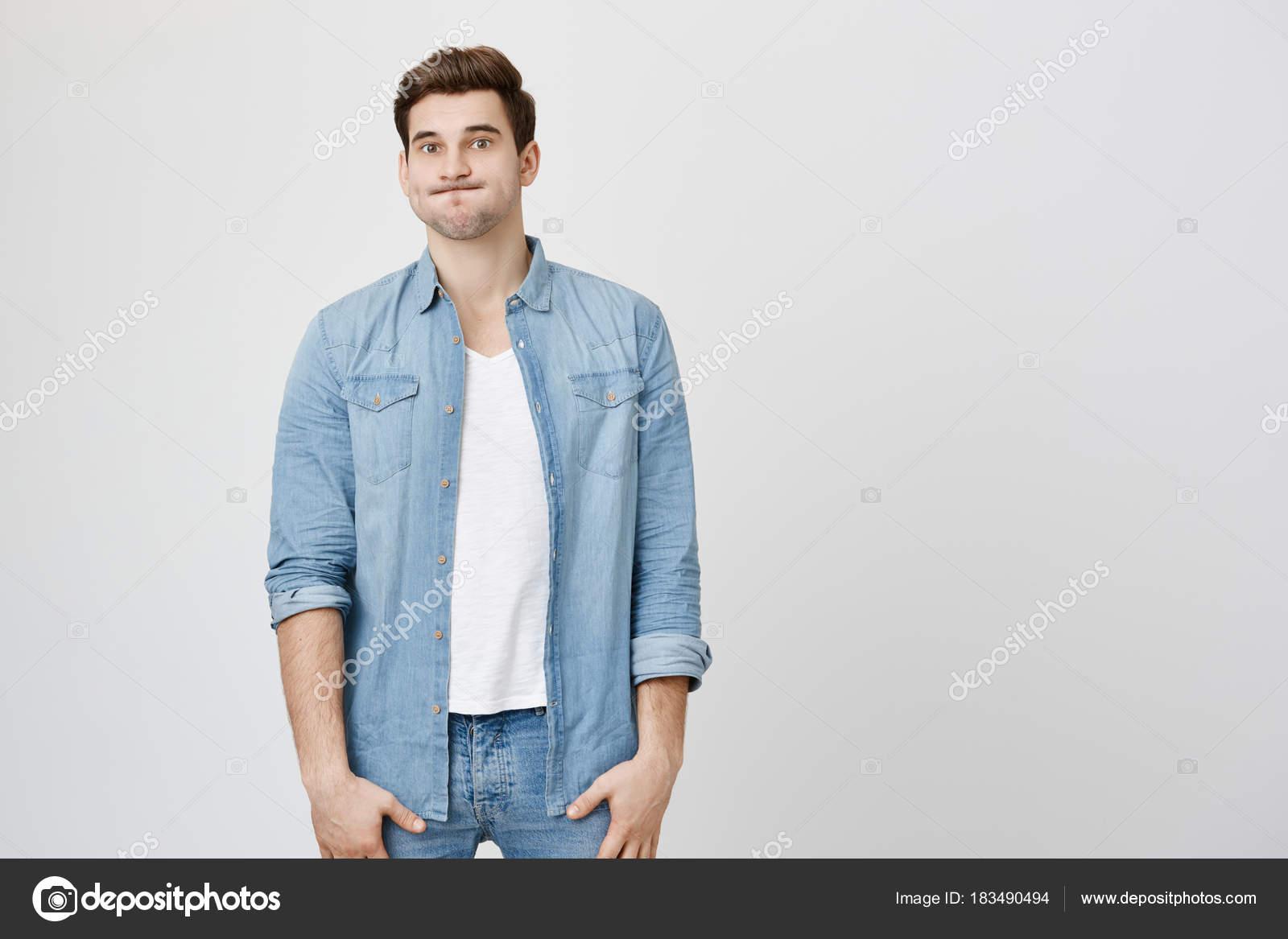 Ratlos und verwirrt schöner Kerl, stehen gerade in Jeans Kleidung ...