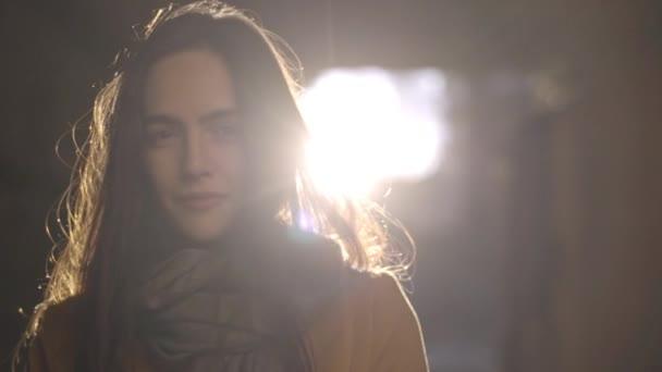 Ritratto di giovane donna dai capelli lunghi essendo illuminata dal sole, in posa sulla fotocamera con bel sorriso al rallentatore. Aspetto cinematografico