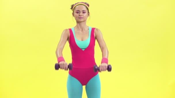 Portrét atraktivní ženy v retro sportovní kombinéza dělá fitness cvičení s malou hmotností, izolované nad žlutým pozadím zpomalené retro