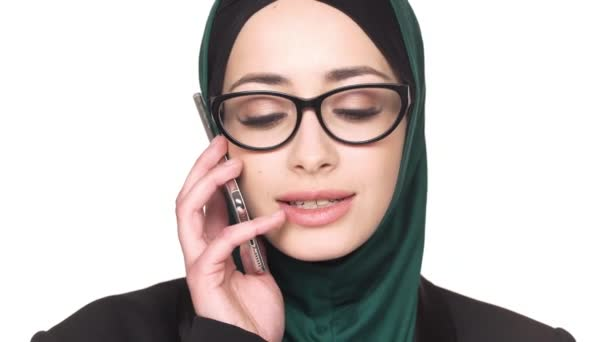 Portrait closeup of lovely muslim woman in headscarf looking at camera and speaking on smartphone, isolated over white background. Communication and technology concept