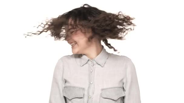 Portrait of fascinating woman 20s with hazel eyes having fun and shaking her head with dark curly hair, over white background. Concept of emotions