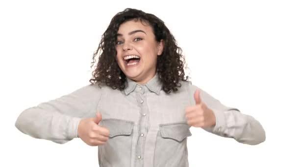 Portrét atraktivní mladé ženy v ležérní košile, která je na fotoaparátu s úsměvem a ukázal palec nahoru nad bílým pozadím. Pojetí emocí