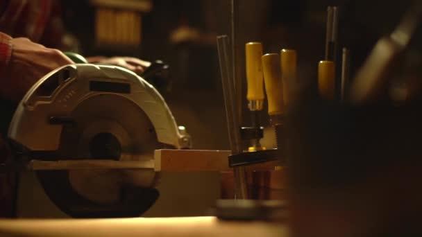 Portrét oříznuté profesionální tesař s dřevěné prkno v obchodě a řezání detail nábytku s kotoučovou pilou Zpomalený pohyb