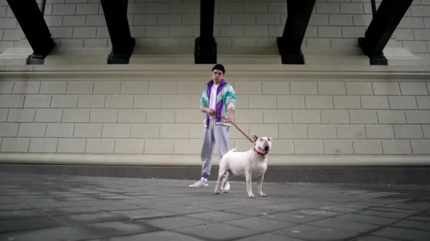 Portrét bokovky guy a jeho psa drží na vodítku, když stál nad stavebních ulici zpomaleně město čistokrevná bullterrier