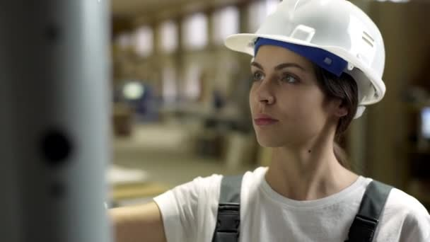 Portrait of concentrated woman wearing helmet and overalls working on furniture factory, and monitoring functioning of equipment