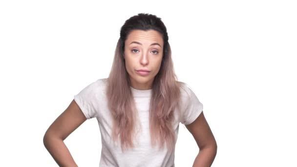 Portrét ženy drzá 20s v ležérní tričko drží ukazováček na rty a důrazně žádá Nerušit, nad bílým pozadím zpomaleně. Pojetí emocí