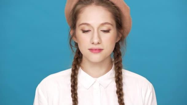 Porträt Nahaufnahme der entzückenden Frau 20er Jahre tragen Baskenmütze und zwei Zöpfe Frisur posiert auf der Kamera mit schönem Lächeln, isoliert über blauen Hintergrund