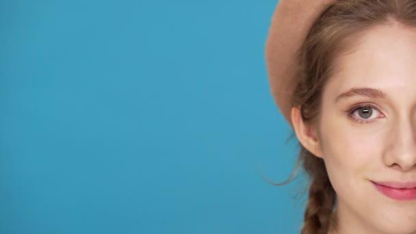 Polovina strany detailní portrét krásná stylová žena 20s nosí baret a dva copánky účes pózuje na fotoaparát s roztomilý úsměv, izolované modré pozadí