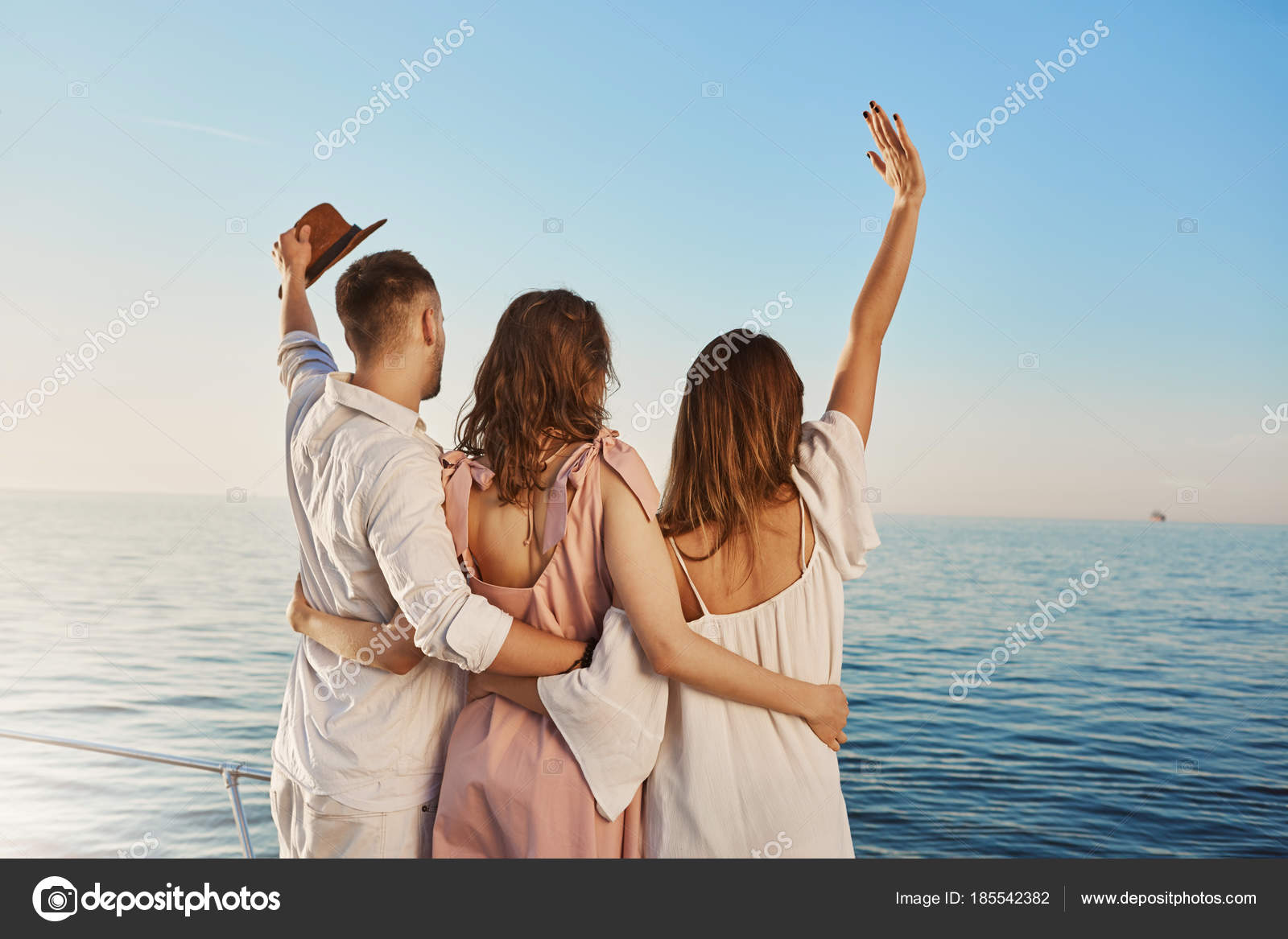 Back View Of Three Best Friends Travelling By Boat Hugging And