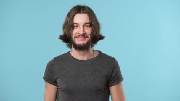 Portrét atraktivní vousatý chlap v neformálním se prsty na kameru, takže Hej, modré pozadí. Pojetí emocí