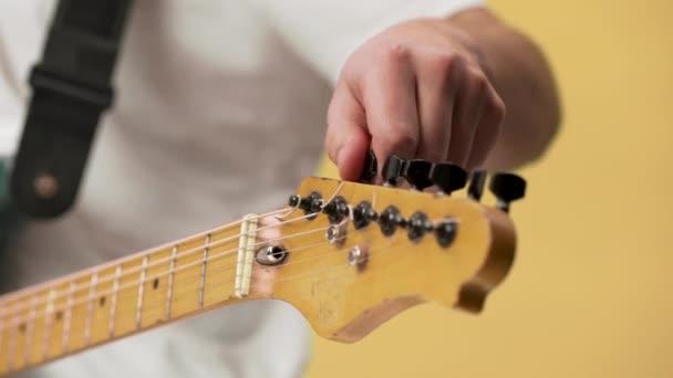 Oříznutí fotografie mladých mužů kytarista v neformálním oblečení oprava ladící kolíky na elektrickou kytaru closeup, izolované žluté pozadí
