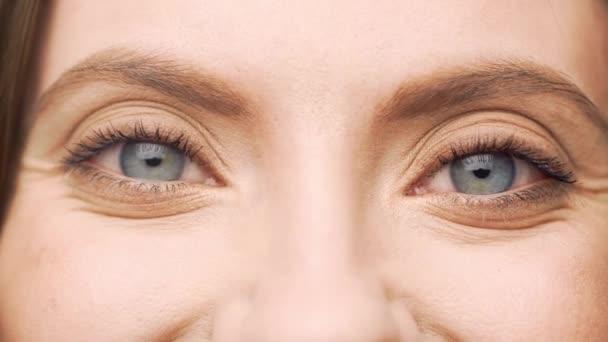 Pozice zcela detailní modrá okouzlující oči středního věku ženy při pohledu na fotoaparát a s úsměvem, izolované nad bílým pozadím ve studiu. Pojetí emocí