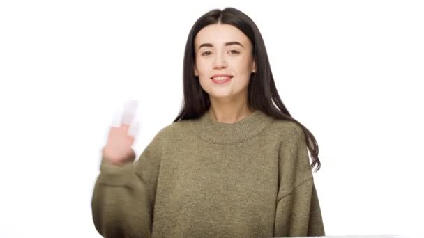 Portrait of positive brunette woman with long hair looking at camera with candid smiling and waving hand meaning hello, over white background. Concept of emotions