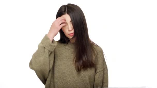 Portrét roztomilý kavkazské ženy vystupují na fotoaparát s hravý vzhled a současně dotýká její dlouhé tmavé vlasy s pozitivním, izolované na bílém pozadí. Pojetí emocí