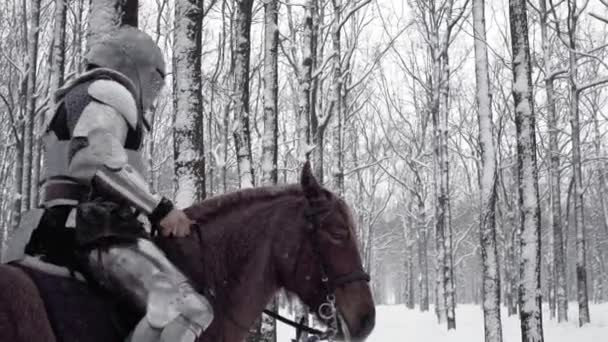Armed medieval knight wearing steel protection and helmet, riding on dark horse through snowy wood in slow motion. Reconstruction of historical battle