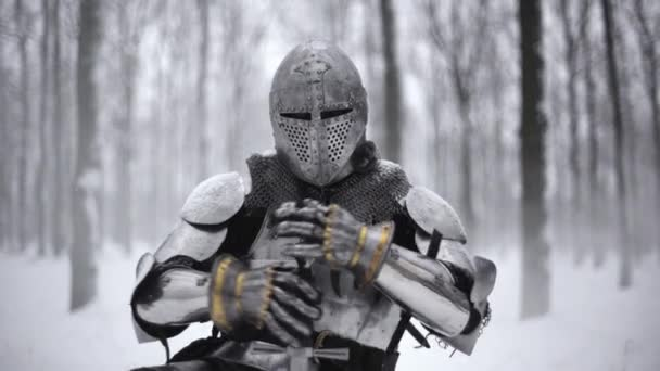 Portrait of medieval knight in helmet holding steel sword and kneeling on winter nature, in slow motion. Fantasy and reenactment