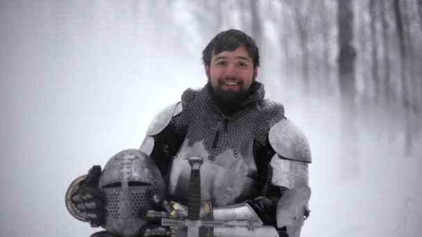 Portrait of young brunette man wearing armor of medieval knight holding his helmet and kneeling on winter nature, in slow motion. Fantasy and reenactment