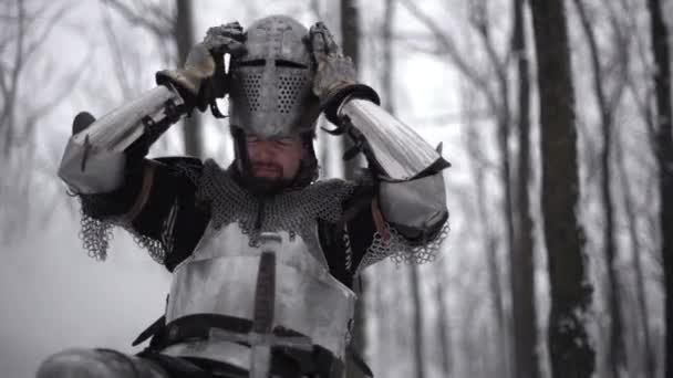 Portrait of medieval warrior putting on steel helmet while kneeling, and holding traditional sword in winter forest slow motion. Fantasy and reenactment