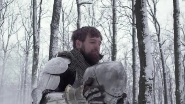 Portrait of male soldier wearing like medieval warrior putting on steel helmet while kneeling in winter forest slow motion. Fantasy and reenactment