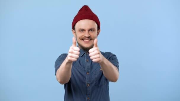 Portrét radostné člověka s kudrnatými vousy a čepice vyjadřuje radost a ukazuje palec nahoru, izolované modré pozadí. Pojetí emocí