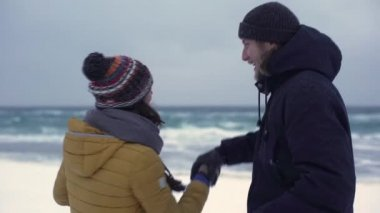 Portrait of cheerful boyfriend and girlfriend dancing at seaside under snowfall and enjoying time together on nature, slow motion