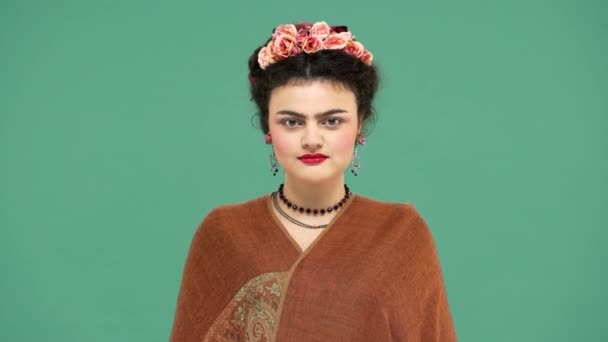 Fashion portrait of woman with flowers in hair as Frida Kahlo posing on camera with playful look, isolated over green background. Stylization concept