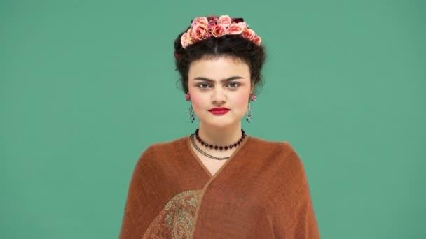 Módní portrét ženy s květy ve vlasech jako Frida Kahlo pózuje na fotoaparát s hravý vzhled, izolované nad zeleným pozadím. Stylizace koncept