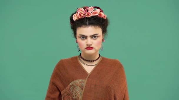 Portrait of woman with thick eyebrows and red lips makeup as Frida Kahlo wearing roses in hair and looking strictly on camera, isolated over green ...