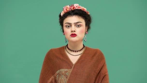 Módní portrét ženy s květy ve vlasech jako Frida Kahlo představuje na fotoaparát s hravý vzhled a dává vzduchu polibek, izolované nad zeleným pozadím. Stylizace koncept