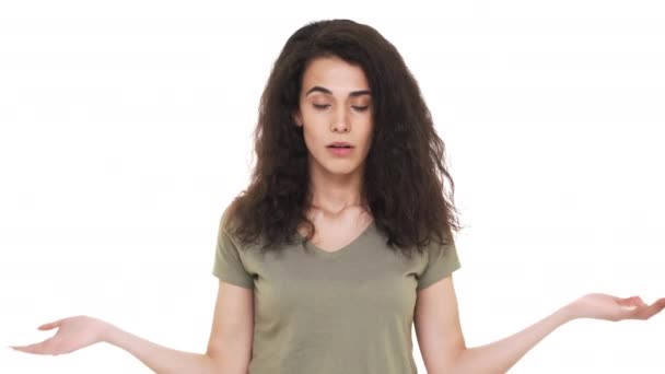 Portrait of hispanic woman with cunning look shrugging and throwing hands  up meaning no information, over white background  Concept of emotions