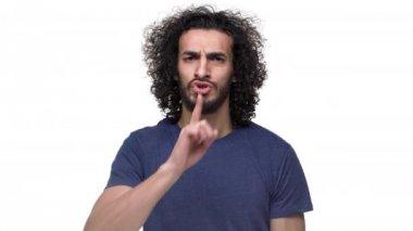 Portrét neoholený kavkazské guy pózuje s přísným pohledem a žádá buď zticha, že ukazováček na rty, izolované na bílém pozadí. Pojetí emocí