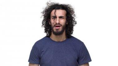 Portrét člověka hansdome v neformálním tmavě modré tričko pózuje na kameru s úsměvem a foukání zámky jeho tmavé vlasy, bílé pozadí v pomalém pohybu. Pojetí emocí