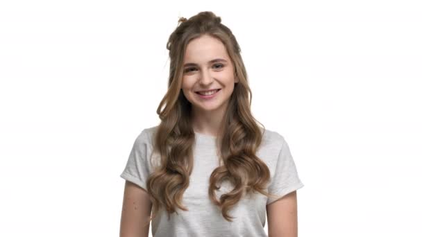 Portrait of attractive woman 20s wearing basic t-shirt expressing joy while looking on camera, isolated over white background in studio. Concept of emotions