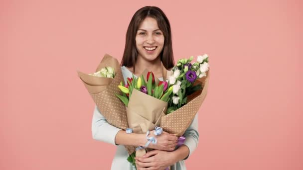 Portrét krásné ženy se šťastným úsměvem drží třemi kytic jarní barevné, izolované růžové pozadí