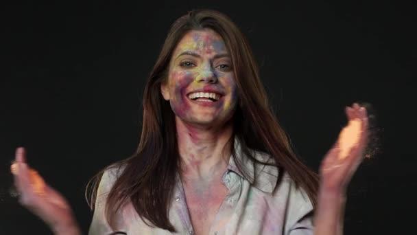 Porträt von begeistert Frau macht Sprung mit bunten Pulver und feiert Frühlingsfest Holi Farben, über Zeitlupe dunkelgrauen Hintergrund isoliert. Indische Kultur und tradition