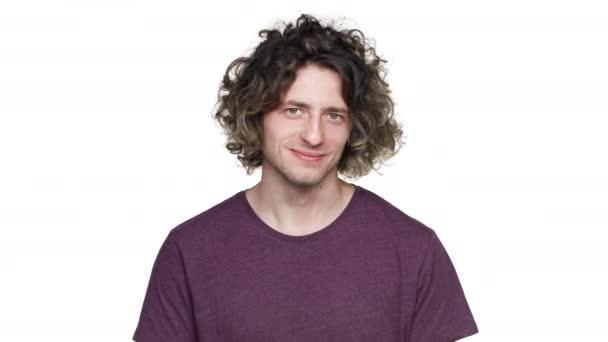Portrét pozitivní neoholený muž v ležérní tričko s úsměvem a ukazující ok symbol s prsty, izolované na bílém pozadí. Pojetí emocí
