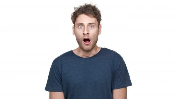 Portrét šokován evropských chlap v tričku při pohledu na fotoaparát a údivu, s otevřenými ústy a s vyvalenýma očima, izolované na bílém pozadí. Pojetí emocí