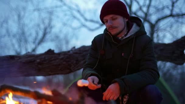 Portrait of caucasian hipster man with mustache smiling, while sitting near campfire outside and frying marshmallows slow motion