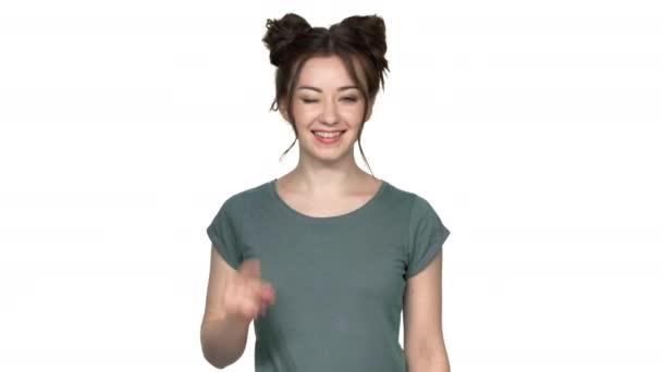 Portrét mladé ženy s dvojitým buchty účes směřují prstem na kameru s úsměvem význam Hej štěstí, izolované nad bílým pozadím ve studiu. Pojetí emocí